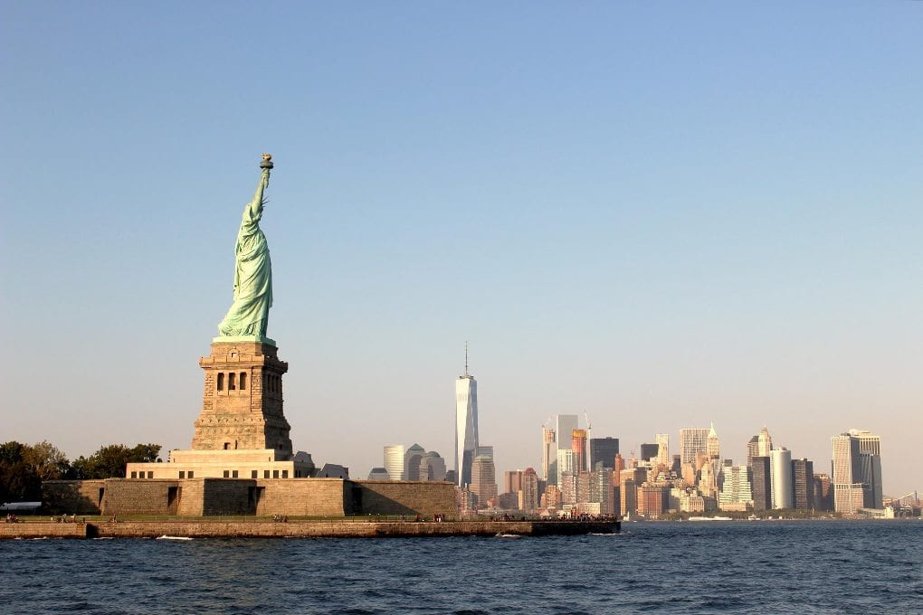 Boat view of ocean and New York City skyline with Statue of Liberty and Empire State Building
