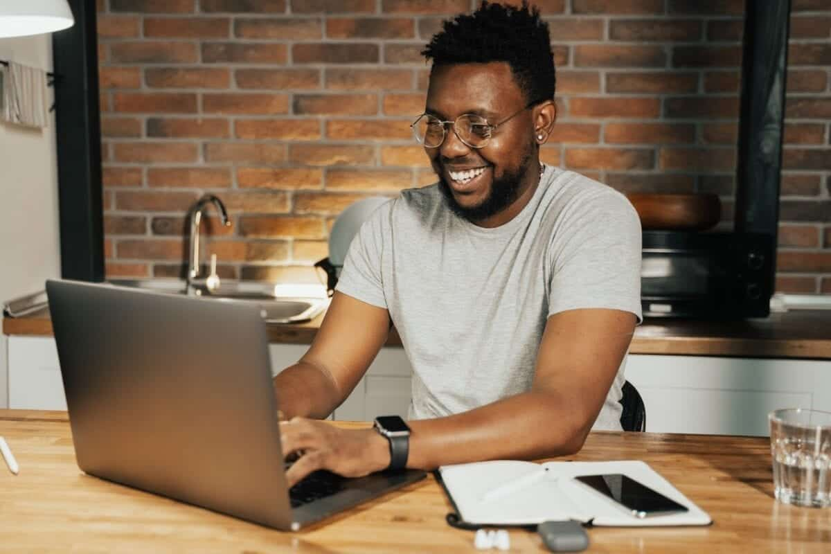 smiling man works on his laptop at his kitchen table