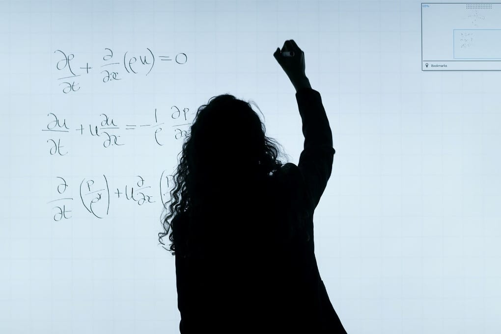 silhouetted person with long curly hair and a raised arm solves math problems on a white board