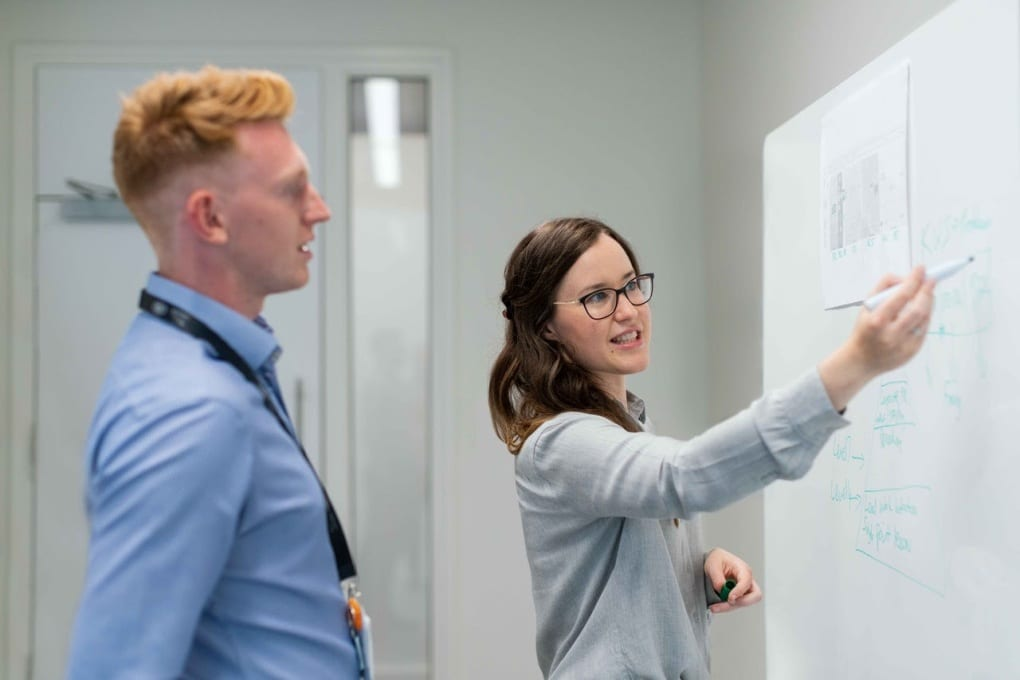 woman holding a dry-erase marker in her right hand explains something to a male colleague, illustrating her point on a white board in front of them