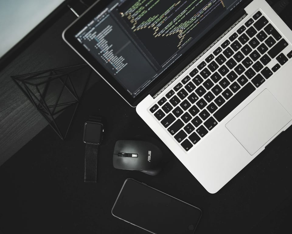 Aerial view of black and silver laptop on black desk next to smartphone and watch