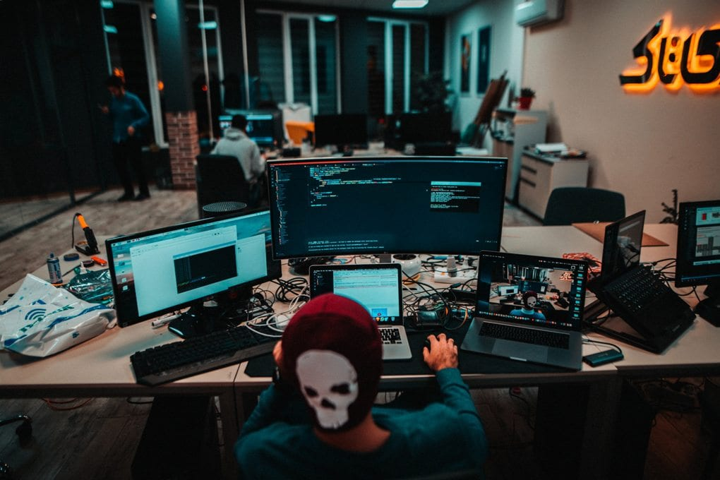 A person wearing a red beanie with a skull picture on it using a laptop. It is on a desk that has many other computers and laptops.