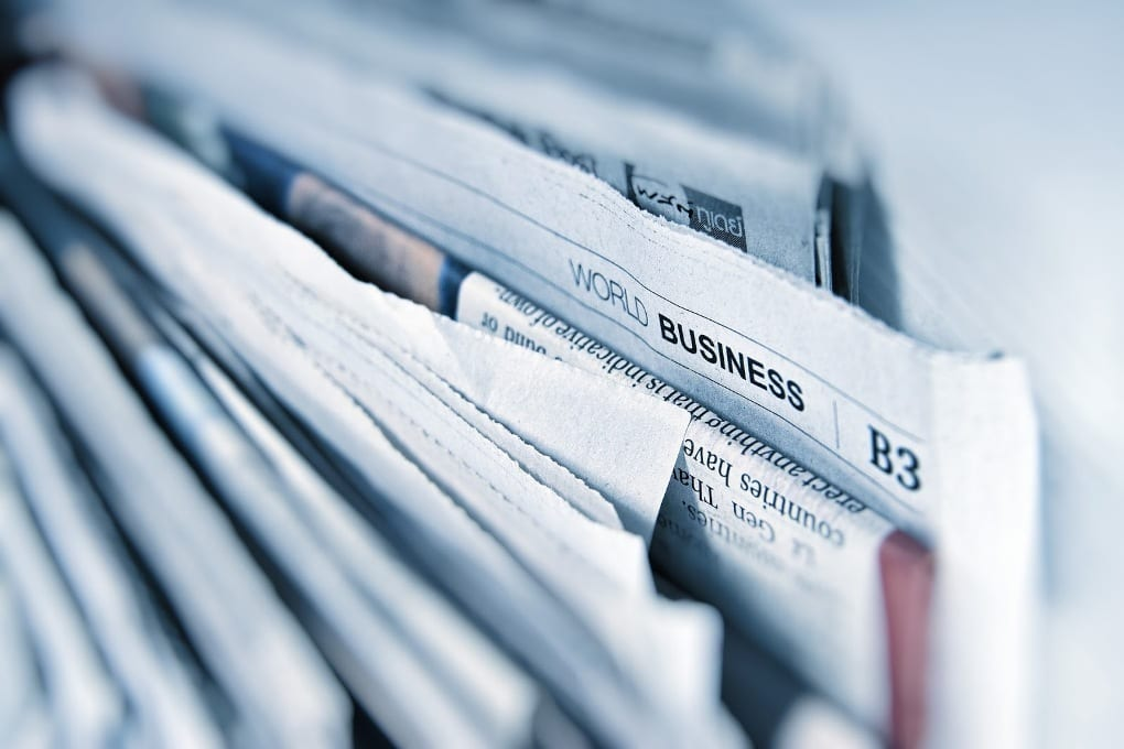 A stack of newspapers. The world business section is visible.