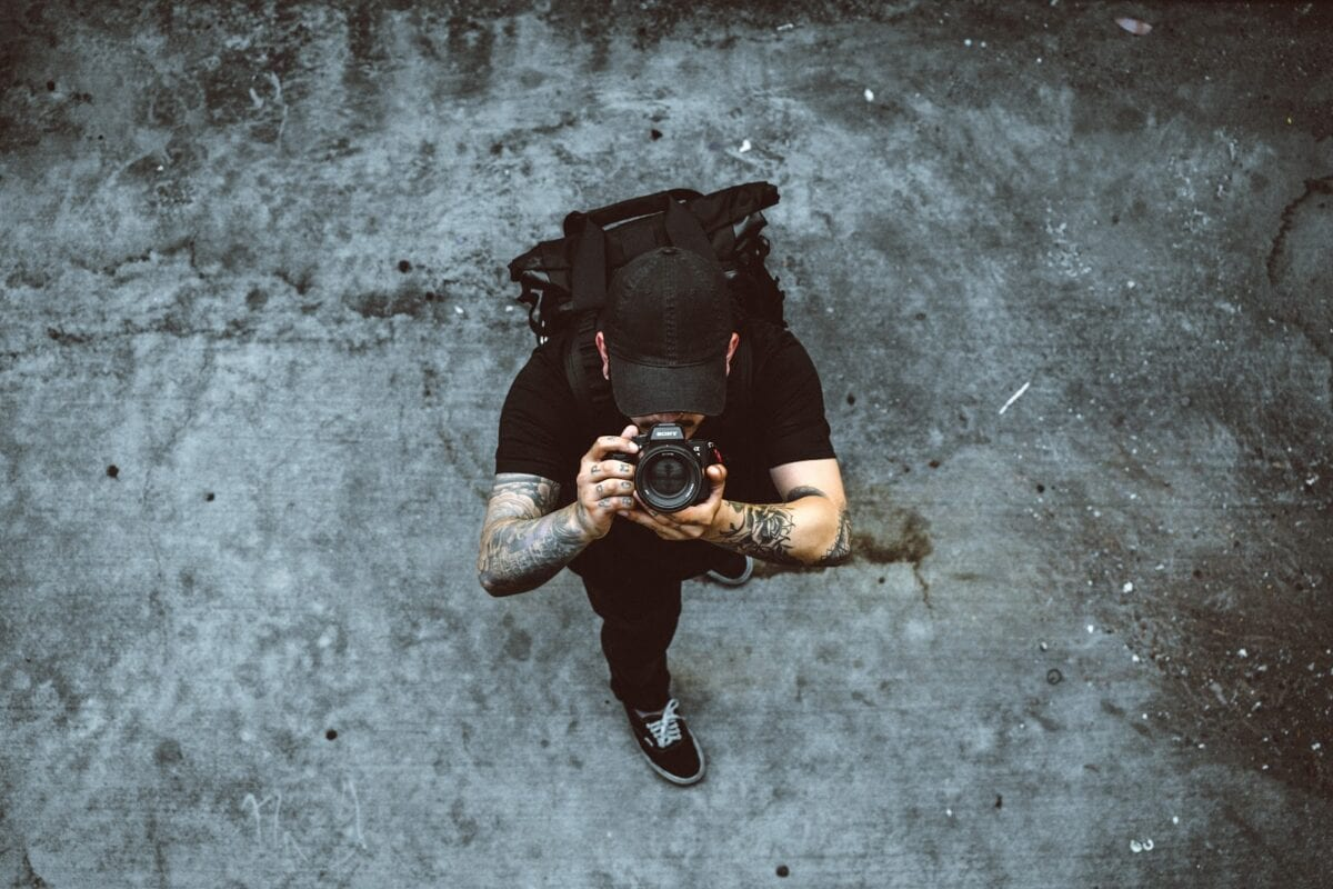 a man in black t-shirt, bag, and cap with tattoos using a Sony DSLR