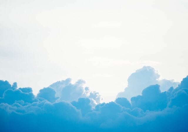 white and blue clouds in a white sky