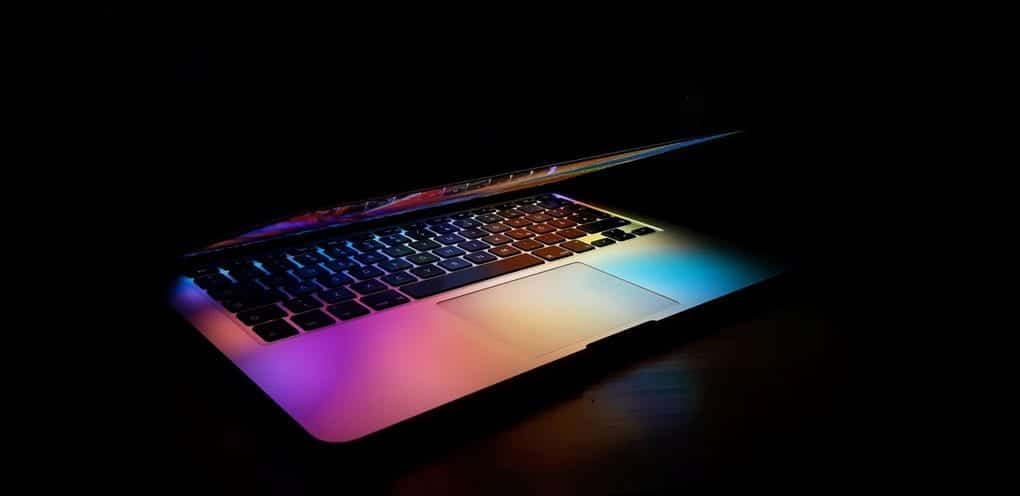 Partially closed laptop reflecting rainbow colors onto keyboard in dark room