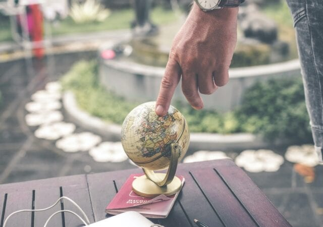 close-up of a person's hand placing the index finger on a small globe, with an outdoor fountain in the background