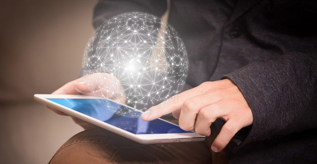 Close-up of a person's hands operating a tablet, the right hand holding it steady and the left hand moving to touch the screen, with a digital image of a cyber network hovering above the device.