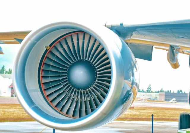 close-up of a jet engine encased in reflective chrome and attached to the underside of a wing, with an airfield in the background