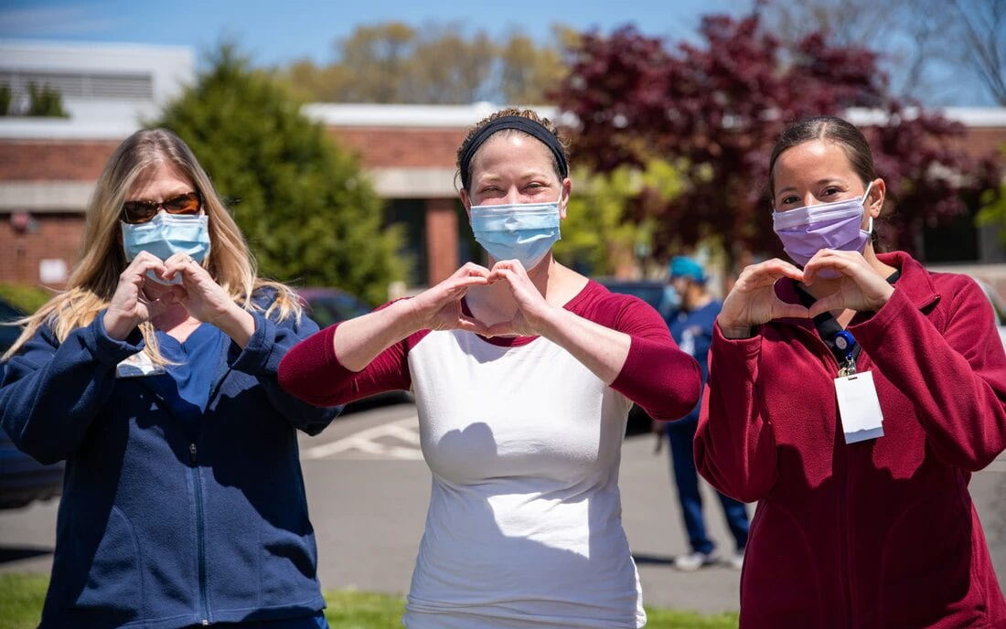 Three nurses standing in masks and making heart signs with their hands.