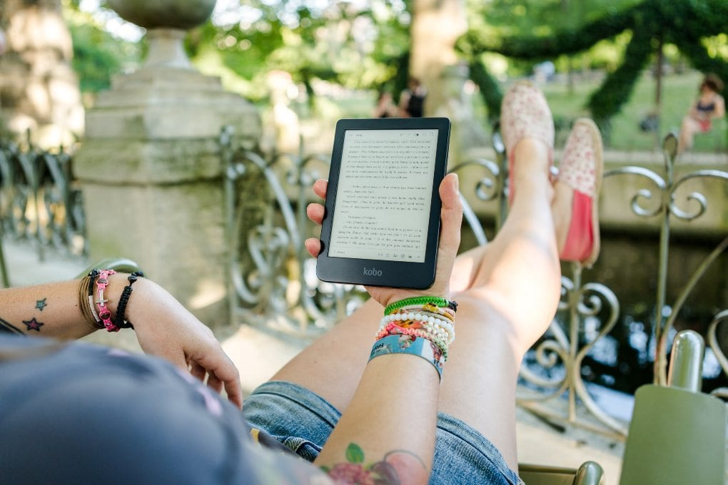 Person wearing multi-colored bracelets, sitting outside and reading book on handheld tablet