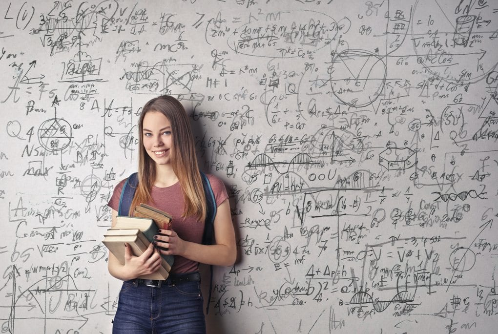 Woman holding a stack of books in front of a wall with math equations and figures scribbled all over it