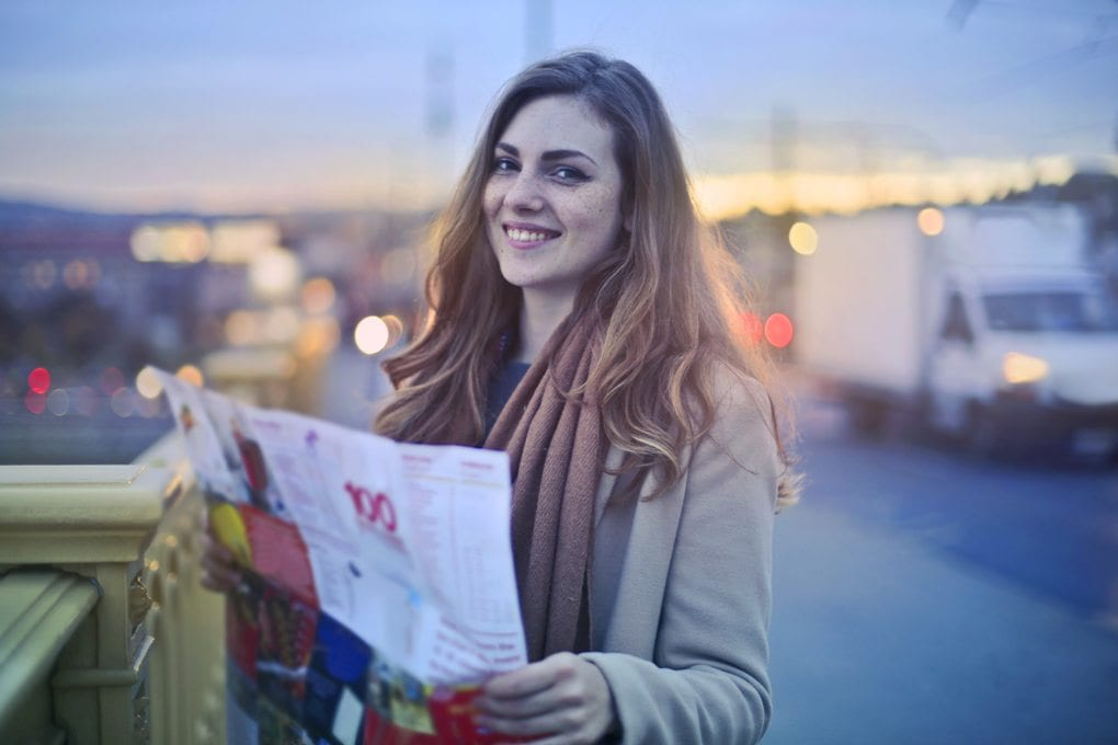 Smiling woman holding a map on a bridge in the evening