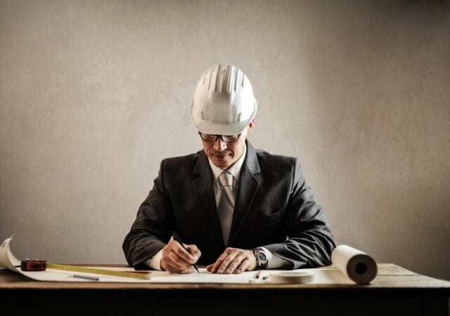 A man in a black blazer and silver tie and white hard hat sketches