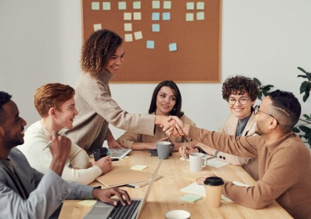 Two people shake hands over a meeting table with six team members sitting around it