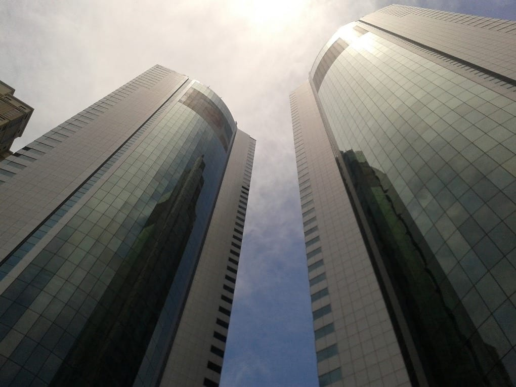 worm's-eye view of two skyscrapers and the sun