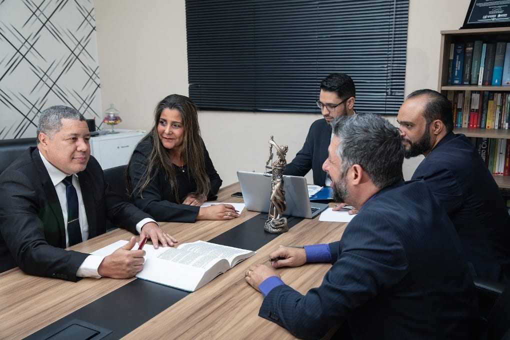 Four men and one woman sitting around a table having an office meeting.