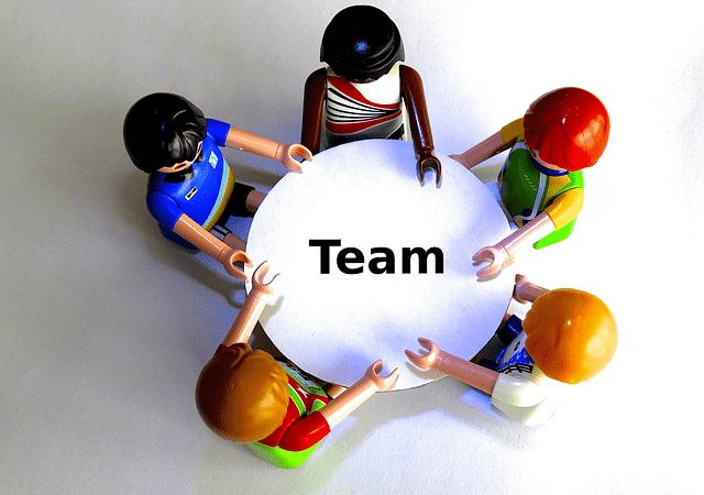 """Five playmobile toy characters sit around a table, where it says, """"team."""""""
