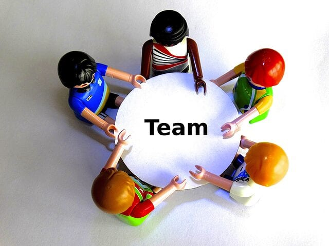 "Five playmobile toy characters sit around a table, where it says, ""team."""