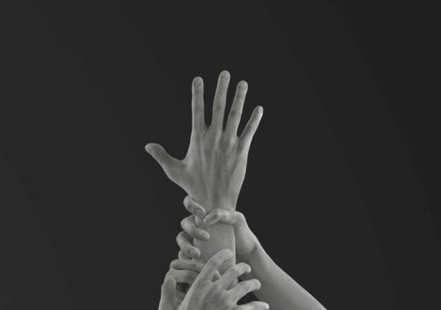 greyscale hand reaching up as other hands grip and pull it down.