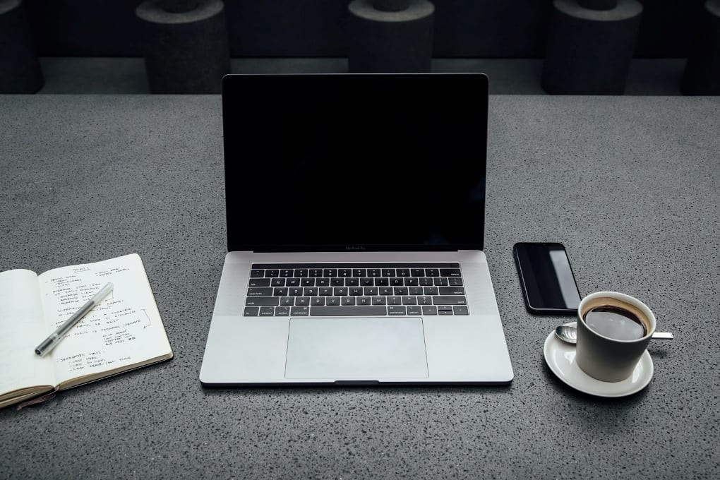 Black and silver laptop on gray desk in between open notebook and coffee mug