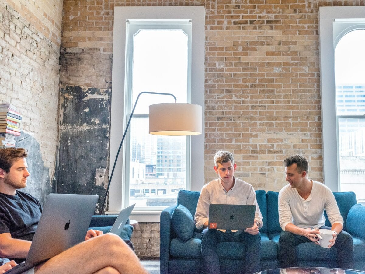 4 men sitting on blue couches on laptops with brick walls behind them