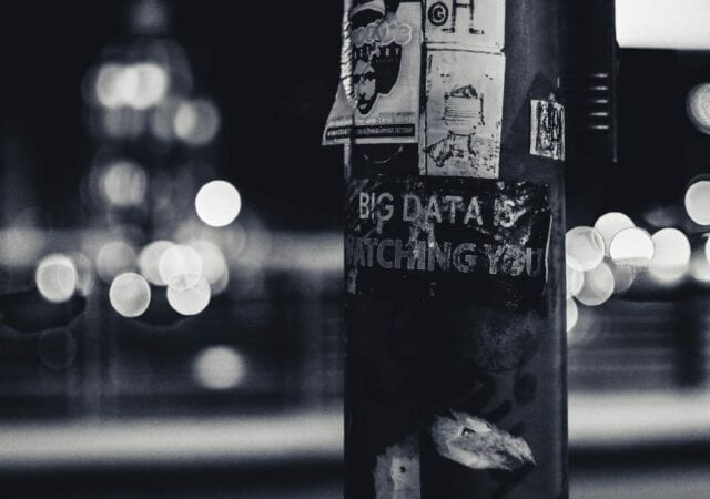 'Big Data is Watching You' pasted on an electrical post in the middle of a street.
