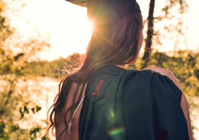 The back of a woman wearing a graduation cap and holding a black graduation gown over her shoulders. The sun's rays are on her. She is in nature, trees around.