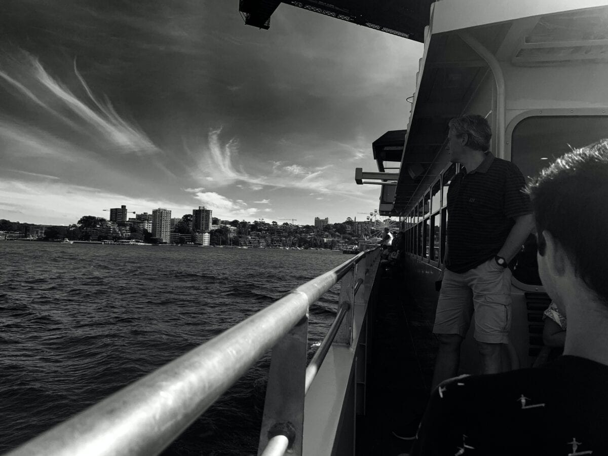 A black and white image of a man standing on a ship looking at the water and the city view.