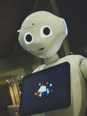 A white robot toy holding a tablet.