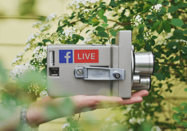 An analog camera with the logo of Facebook and a LIVE sticker on it