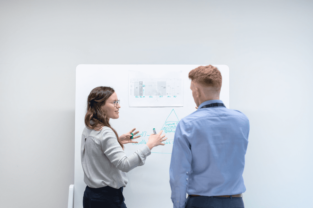 woman showing coworker her work on a whiteboard