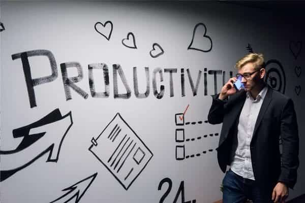 A man standing in front of a white-board talking on his phone. On the board is the word PRODUCTIVITY written in black ink with large letters and other images like arrows, pages, and a checklist with a red tick inside a box.