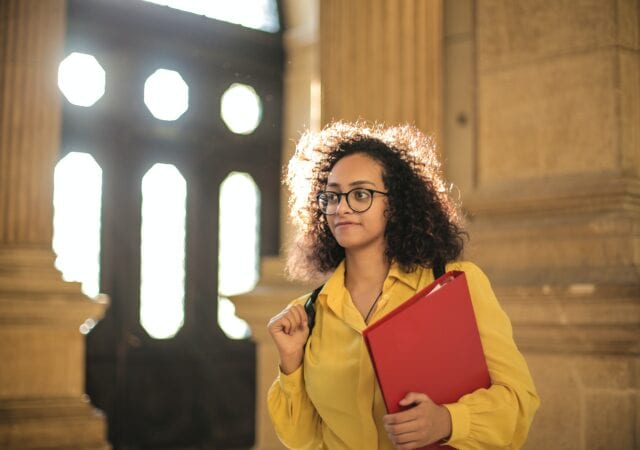 Female student in yellow carrying a red binder