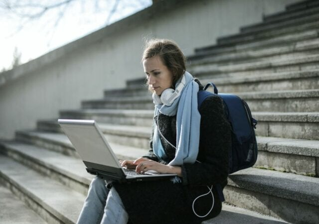 Woman sitting on a stone staircase working on a laptop computer