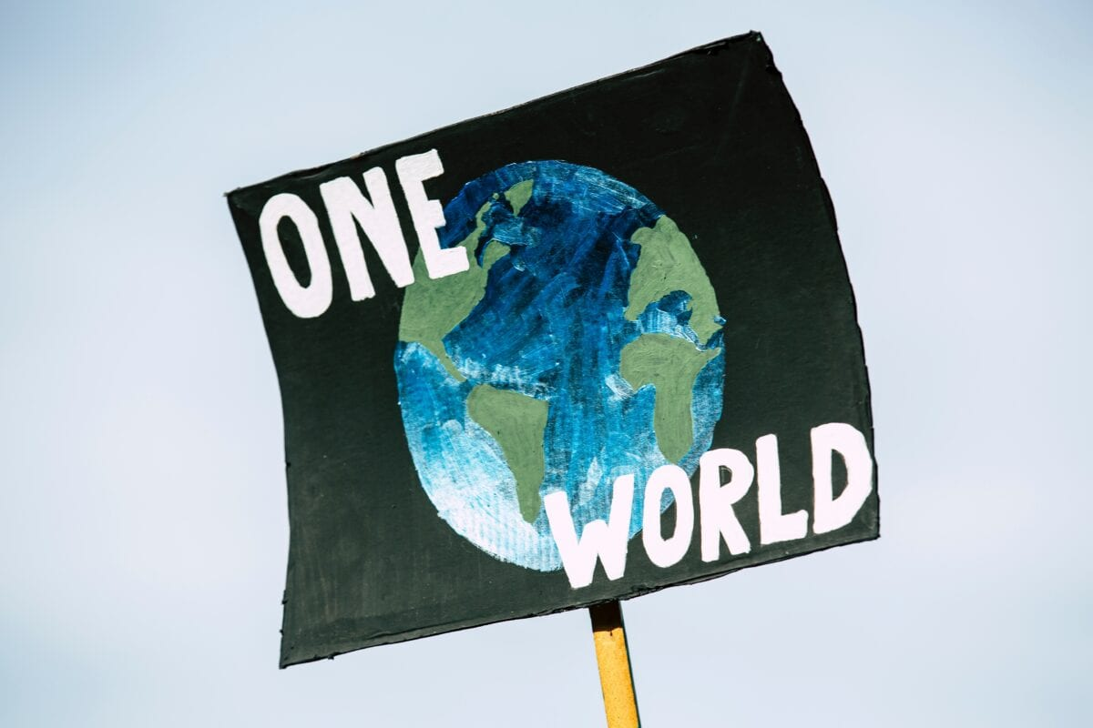 A protest sign that says One World with a hand-drawn image of the world.