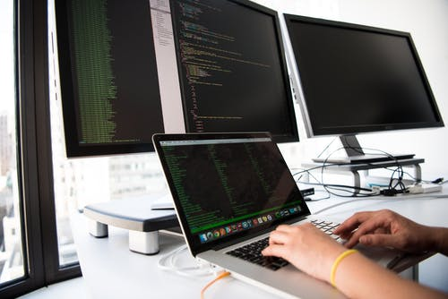A picture of a developer checking data from different computer sources.