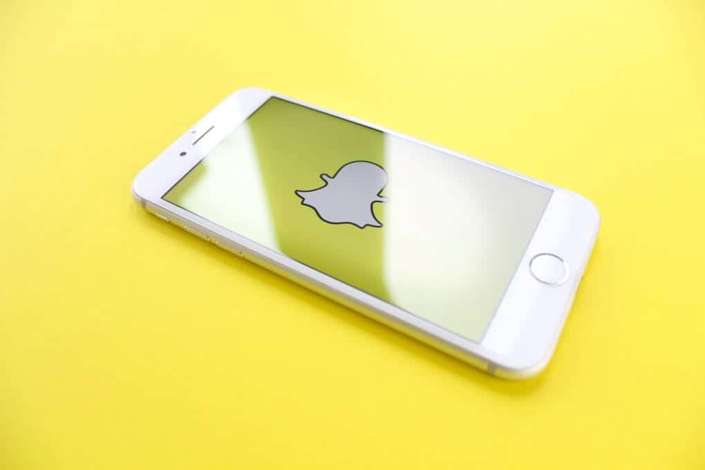 a white iPhone on a yellow surface with the Snapchat logo on the screen