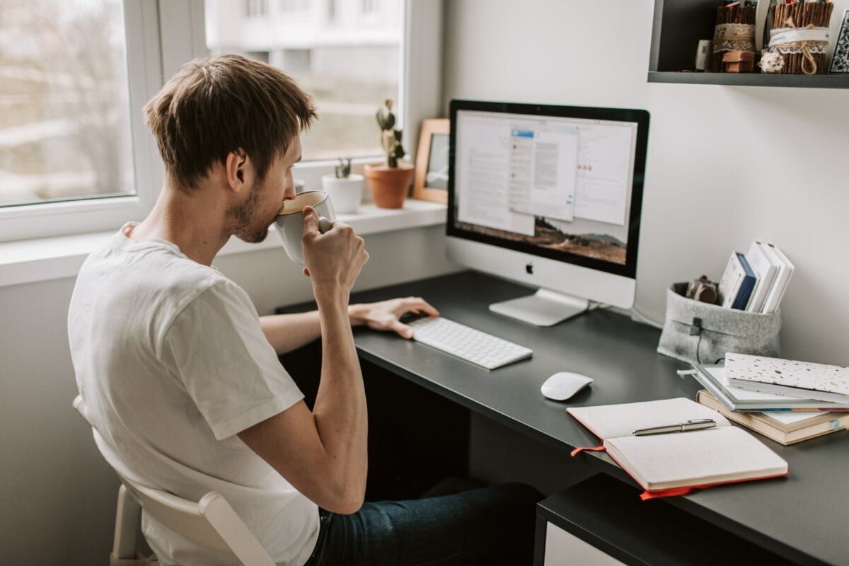 Man in white shirt sitting at a desk drinking coffee in front of a Mac computer