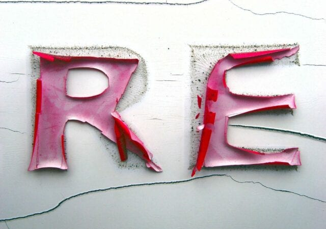 close up photo of R and E, painted red, but with paint peeling off.