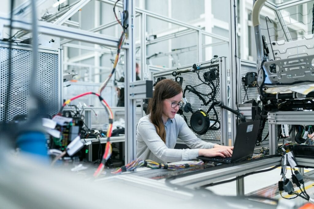 Female electronics engineer running vehicle tests on a laptop