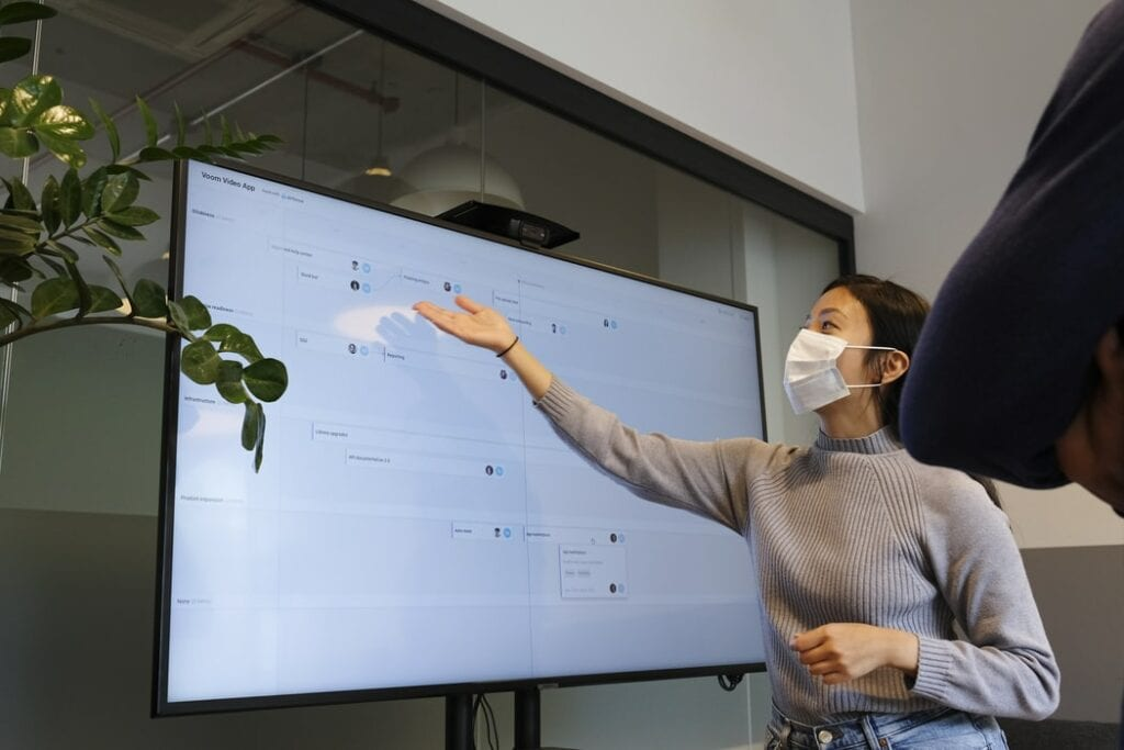 Women wearing mask giving a presentation on a large screen