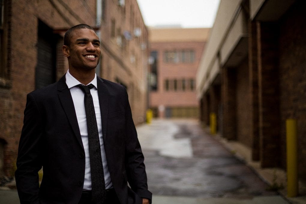 a man in a nice suit standing in an alley
