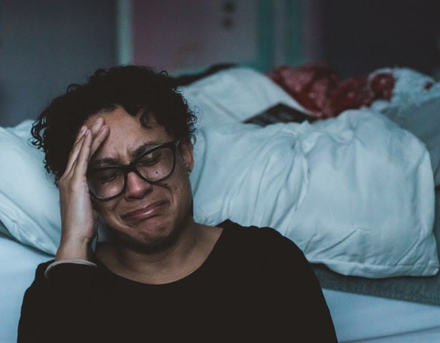 A person crying beside a bed