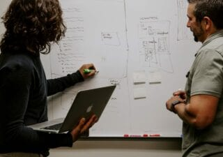 two people working at a whiteboard