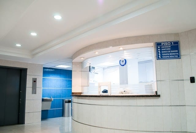 White tile walls and an empty reception desk.