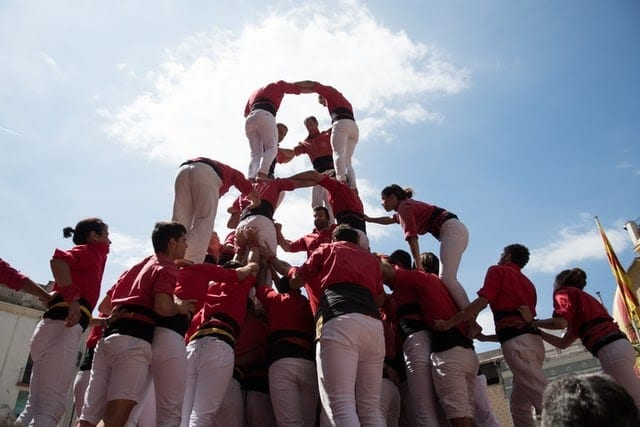 Group of people dressed in red and white making a human pyramid