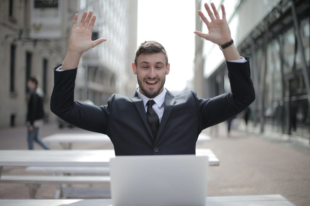 Man in suit celebrating with his hands raised high