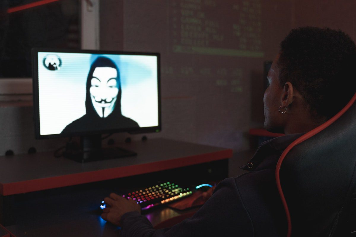 Person looking at a hacker on a computer screen How to Become a Cyber Security Analyst