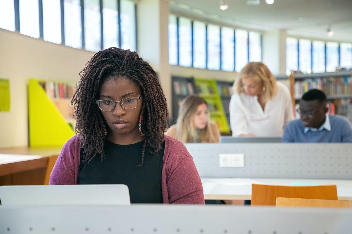young female college student working in the library on homework for her postsecondary classes How to Become an IT Support Specialist